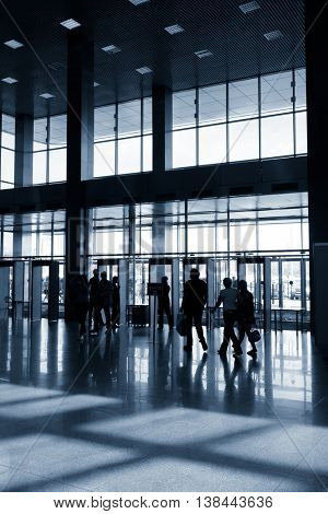 Silhouettes of people in modern lobby. Translation of the inscription is Exit