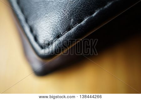 Macro detail of a dark thread stitching black and brown stitched leather wallet
