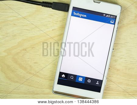 BUNG KAN THAILAND - JANUARY 15 2016: smart phone display instagram app is charging battery