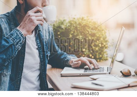 Enjoying fresh coffee. Cropped image of young man drinking coffee and working on laptop while sitting at sidewalk caf