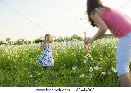 A Mother and daughter blowing soap bubbles