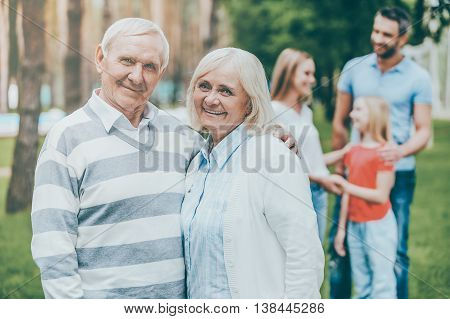 Happy seniors. Happy senior couple bonding and looking at camera while other family members standing in the background