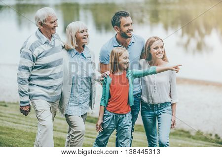 Family time. Happy young family walking outdoors together while little girl pointing away and smiling