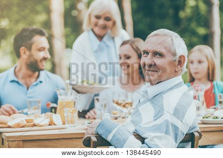 Enjoying great time with family. Happy family of five people sitting at the dining table outdoors while senior man looking over shoulder and smiling
