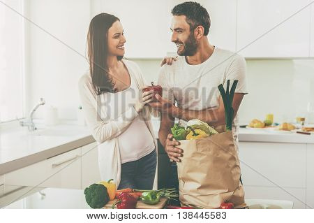 Living a healthy life. Beautiful young couple unpacking shopping bag full of fresh vegetables and smiling while standing in the kitchen together