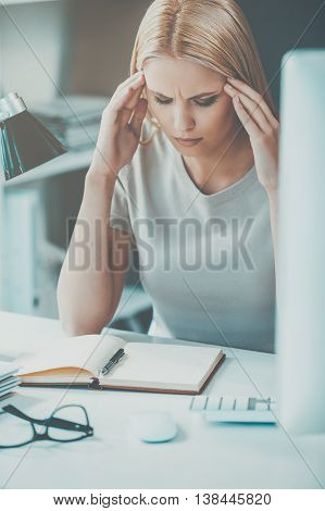 Feeling stressed and exhausted. Frustrated young woman touching her head and keeping eyes closed while sitting at her working place in office