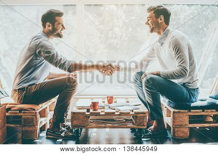 Men shaking hands. Side view of two happy young men shaking hands while sitting in front of the window