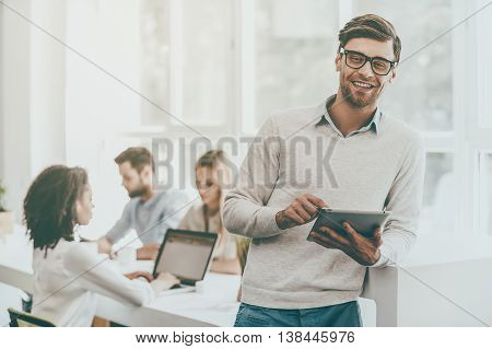 Young and successful. Happy young man holding digital tablet and looking at camera while his colleagues working in the background
