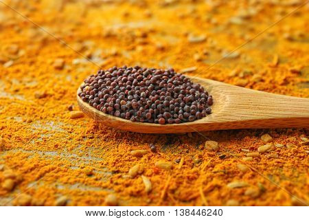 Black mustard seeds in wooden spoon on mixed spices background