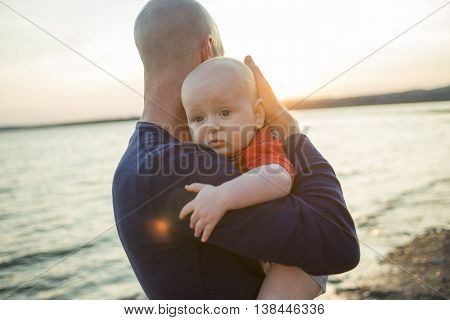 A happy joyful father with baby on sunset