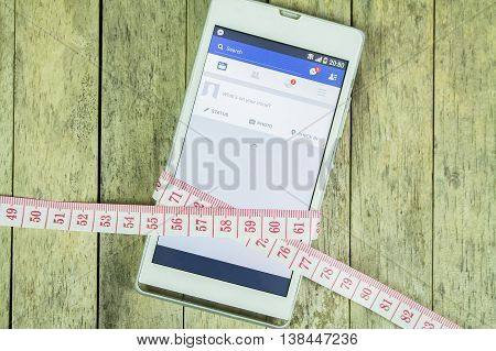 BUNG KAN THAILAND - FEBRUARY 21 2016: smart phone display facebook app and measure tape on office desk