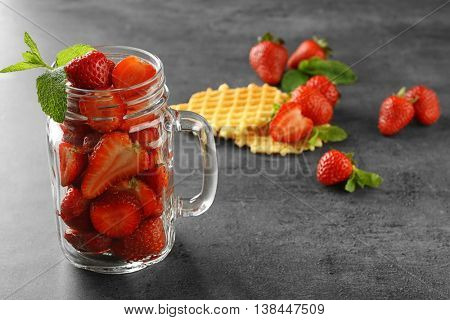 Tasty strawberries in glass jar with wafers on table