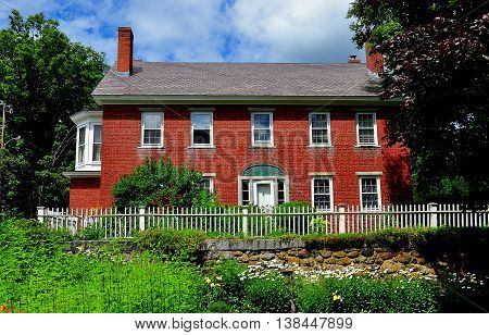 Harrisville, New Hampshire - July 12 2013: Handsome early 19th century brick home with picket fence and gardens in the historic district