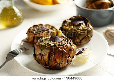 Baked artichokes on white plate