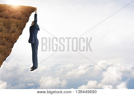 business concept challenge businessman clinging on to a cliff