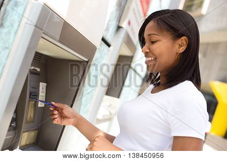 young woman at the cash machine withdrawing money