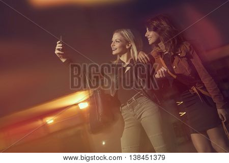 Two beautiful girls taking a night lights selfie on the street before going out to a nightclub