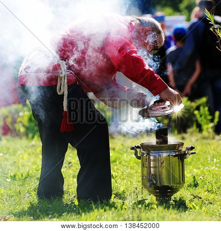 Orel Russia - July 08 2016: Russian Valentine Day - Petr and Fevronia. Man in Russian suit lighting samovar closeup