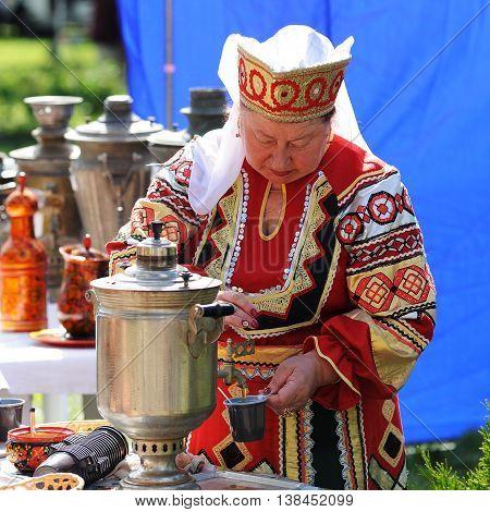 Orel Russia - July 08 2016: Russian Valentine Day - Petr and Fevronia. Senior woman in Russian dress making tea in samovar closeup