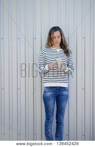 Young Woman With A Cup Of Latte On Metal Background