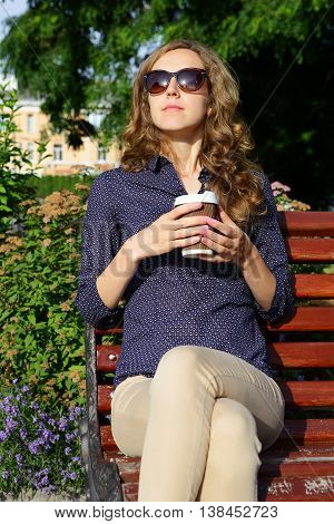 Stylish Blonde Woman In Sunglasses With Disposable Coffee Cup Sitting On Bench