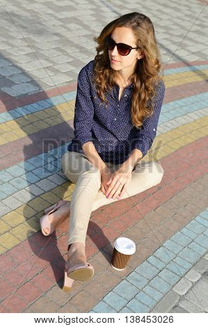 Stylish Woman In Sunglasses With Disposable Coffee Cup Sitting On Pavement Cobblestone