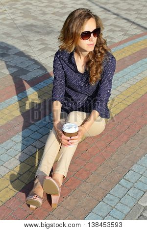 Stylish Woman In Sunglasses With Disposable Coffee Cup Sitting On A Pavement Tiles