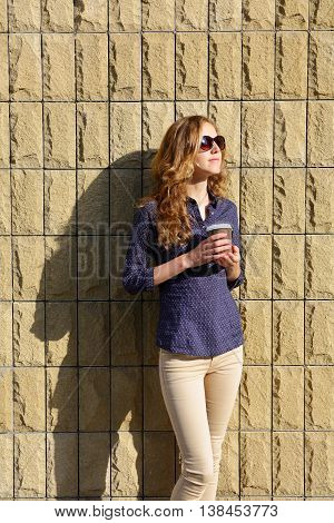 Stylish Woman In Sunglasses With Disposable Coffee Cup Against The Background Of Brick Wall