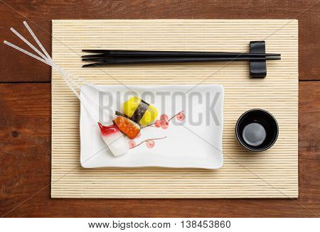 Beautiful colorful lollipops in the form of sushi lying on white square plate with pink flowering tree pattern standing on bamboo mat and brown wooden table with black chopsticks and sake cup.