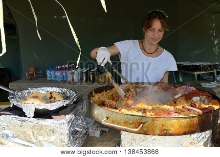 KERNAVE, LITHUANIA - JULY 7: Unidentified people make food at 14th International Festival of Experimental Archaeology on July 7, 2013. Its a most popular folklore event on July in Lithuania