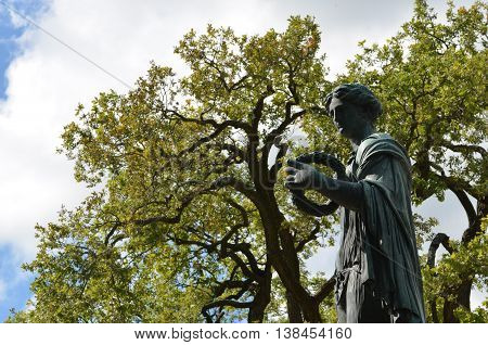 Antique Catherine park in Saint Petersburg, Russia. Summer landscape. Nice bronze statue of roman goddess Flora with floral wreath on the front plane. Green branches of big trees.