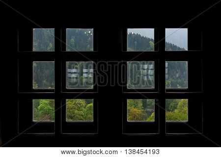 View of Austrian Woods in Tirol through Silhouetted Small Square Windows