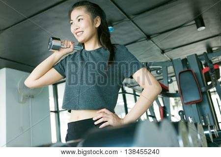 Portrait Of Pretty Asian Girl Training In Gym Lifting Barbell