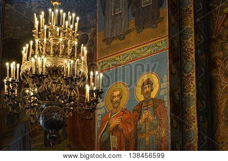 Saint Petersburg, Russia - August 23, 2013 - Church of the Savior on Blood interior. Colorful paintings, mosaic murals. Figures of saints. Chandelier. Poorly light, dark environment, selective focus.