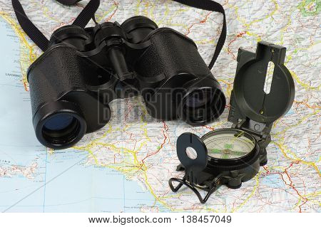 Porro binoculars and military compass lying on the map.