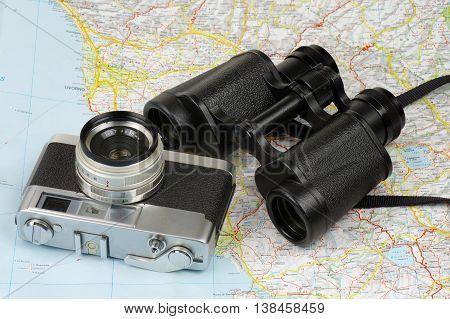 Porro binoculars and old rangefinder analog camera lying on the map.