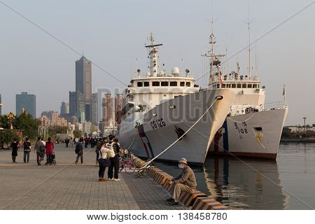 Kaohsiung, Taiwan - January 11, 2015: People at the harbor front with anchored ships