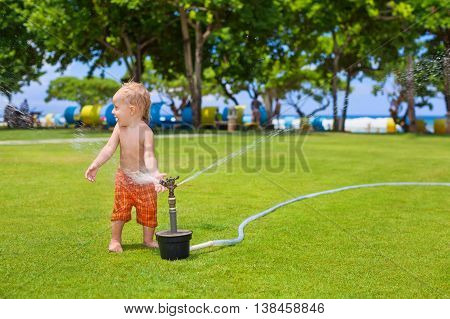 Happy baby boy playing with sprinkler water spray and splashing with fun on green grass lawn. Travel active lifestyle people activity on summer beach vacation with children.