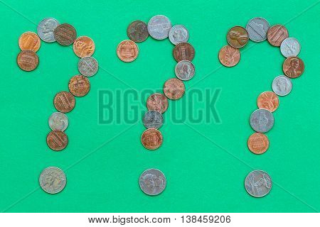 Coins forming three question marks on green background