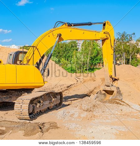 Yellow excavator on a construction site at summer day time.