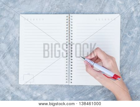 Closeup woman hand writing on note book on concrete desk in top view textured background under day light in the garden