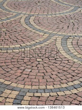 Closeup of sidewalk paving bricks pattern in red, black and yellow