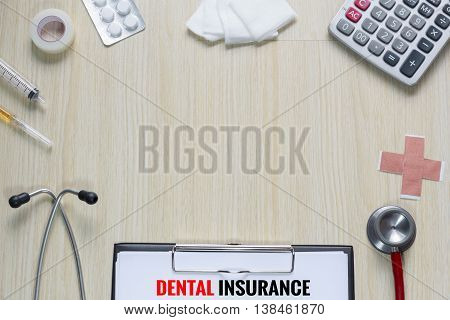 Top view of dental insurance with stethoscope hypodermic syringe plaster gauze calculator and tape.