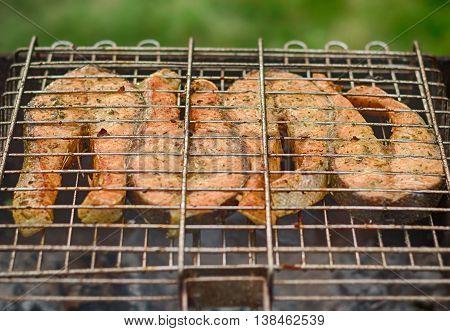 Fresh fish on grilling sticks. Fried Salmon