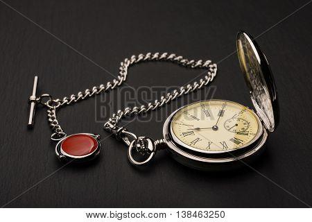 Stylish retro pocket watch on black slate background