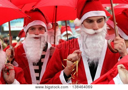 Uzhgorod Ukraine - December 19. 2008: Young people under the red umbrellas dressed as Santas are marshing the city's streets during the Parade of Santa Clauses.