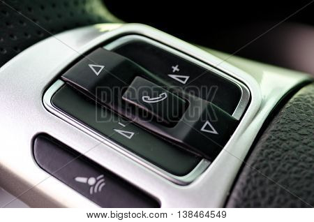 Car control keys for radio volume on leather steering wheel