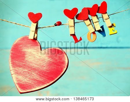 Heart with letters hanging from clothespins on a blue background