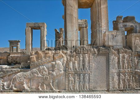 Palace in ruins with ancient bas-relief of Zoroastrians and figures of people and animals in Persepolis, Iran. Persepolis was a capital of the Achaemenid Empire 550 - 330 BC.