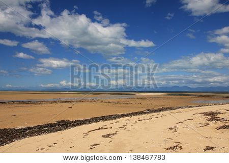 Marahau beach at low tide and summer clouds. Scene in New Zealand.